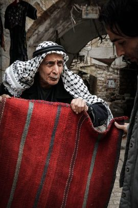 photo of man selling carpets