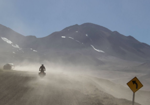 motorcycle following a car on a dusty road